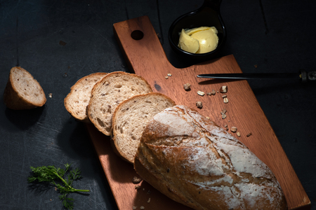 Pain de campagne  Or country bread in French On Wood Plate  And Steel Table With Cup Of Butter.