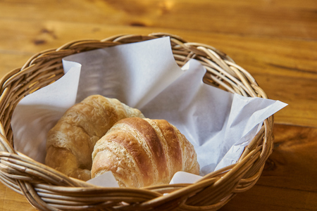 Close Up Of Croissant In Basket On Wooden Table. Stock Photo