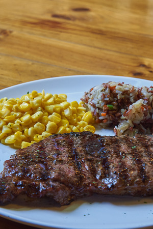 Close up Of Wagyu beef Steak In White Disk With Sweet Corn And Herb Rice, Selected Focus