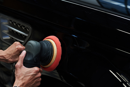 Hands with daul action polisher. polishing on car surface. foam pad in blur motion from vibration of polisher machine