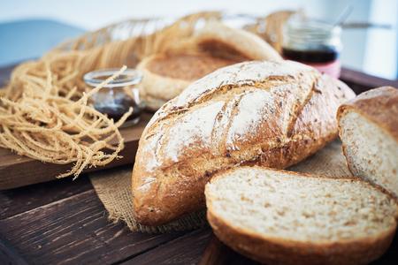 Frisches Brot auf Holztisch mit Butter und Mix-Obst-Marmelade.