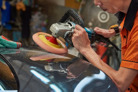 Hands Polishing Car With Rotary Car Polisher. Polishing On Car Paint Surface. Foam Pad In Blur Motion From Vibration Of Polisher Machine. Selected Focus Archivio Fotografico