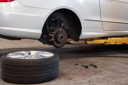 Car Lifted In Auto-Repair Service For Fixing And Tire Lay Down On Floor.