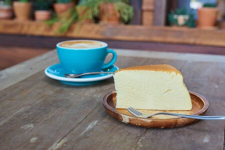 Piece Of Japanese Cheesecake In Wooden Plate And Blue Cup Coffee Blackground.
