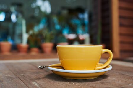 Yellow Cup Of Coffee With Latte Art On Wood Table
