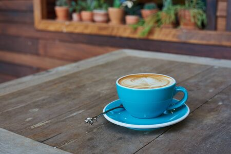 Blue Cup Of Coffee With Latte Art On Wood Table