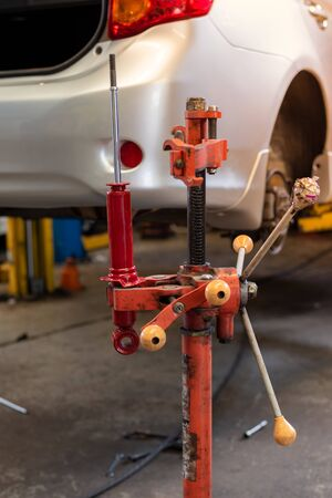 Red Car Absorber Hang On Red Absorber Changing Machine In Auto-Repair Service.