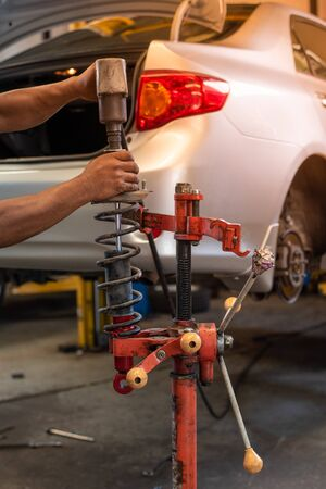 Hands Changing Car Absorber With Red Machine In Auto-Repair Service.