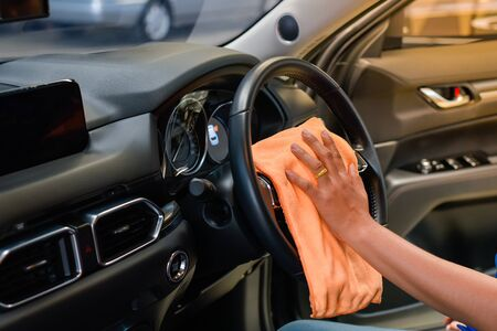 Hand with microfiber cloth cleaning car interior, Fucus  On Hand.