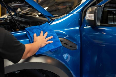 Hand with Blue microfiber cloth cleaning car, Fucus  On Hand
