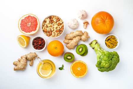 Food for immunity stimulation and viruses protection. Broccoli, citrus fruits, honey, ginger, lemon, garlic, goji, turmeric on white background. Set of different healthy food to boost immune system