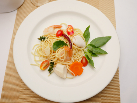 marinara sauce: Spaghetti stir fried. It has a spicy taste with shrimp and squid in white plate. Stock Photo