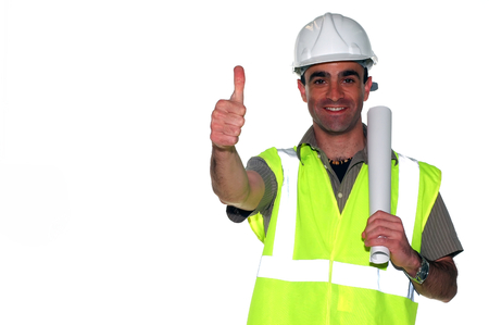 yellow hard hat: happy spanish construction worker with an architectural plans showing his thumbs up