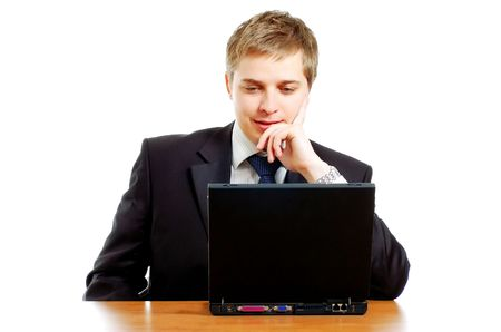 Thoughtful young businessman sitting behind the computer photo