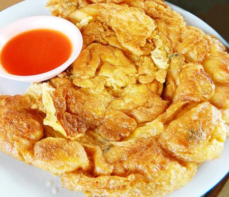 plato de comida: tortilla de estilo tailandés en un plato servido con un tazón de salsa de chile Foto de archivo