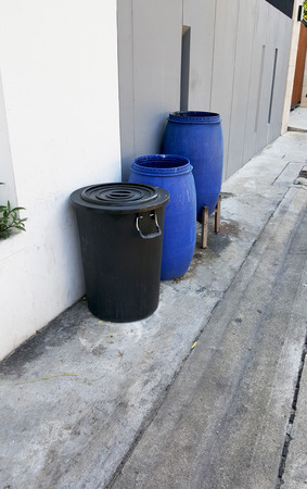 blue bin: Empty blue and black plastic garbage bin or trash can in front of the house