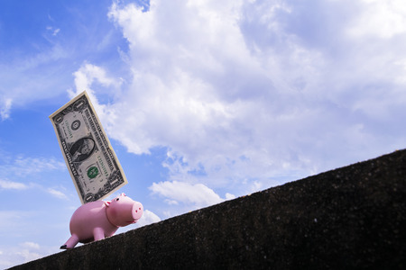 Piggy bank with a dollar plugged in. Walking up steep slopes The backdrop is a bright sky