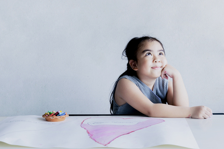 The girl is imagining what her future will be like, artwork is essential for the child, children is working art with chalk color.