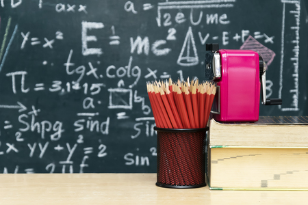 Many red pencils Set in a circular arrangement,eraser,Pencil sharpener Put on the table,The backdrop is Blackboard with mathematical content,Writing with a variety of colors,To stimulate teaching.