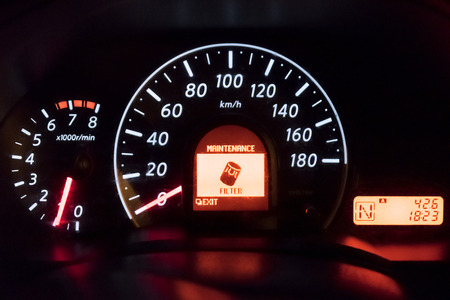 Detail of the dashboard of a car, with the oil alert icon lit up, Oil Change Symbol.