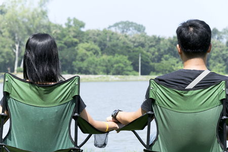 Men and women traveling in nature, looking at the forest, ponds, They both love each other hold hands warmly, Sit on a green fabric chair. 写真素材