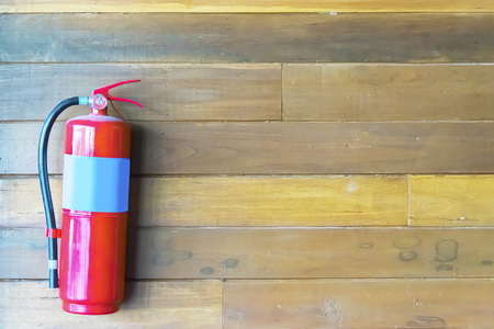 Safe build It is a solid supplement to the family, a fire extinguisher installed at home to prevent fire, red tank, wooden wall. 스톡 콘텐츠