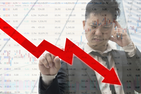 Businessman serious with stock fall, serious expression with stock market,Down trend direction of graph with Stock down symbol.concept of down and finance Red arrow fall dawn,economy.