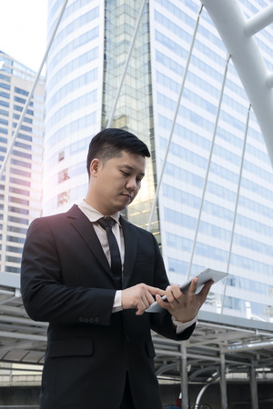 Officials are working on a tablet,Construction plan to business,wearing a black suit,White shirt,The path of capitals prosperity,Real Estate Business Investment Plan Check the market demand.