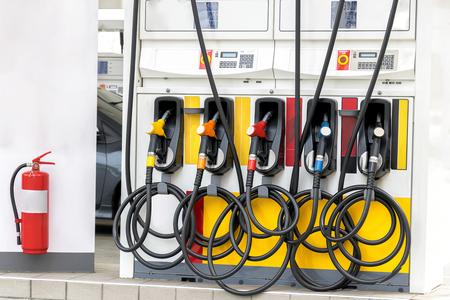fuel oil gasoline dispenser at petrol filling station,Fire extinguisher is installed for safety.