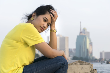 Asian women are feeling very strain,Wearing a yellow shirt,jeans,The hand is holding the hair on the head,Sitting on the river.