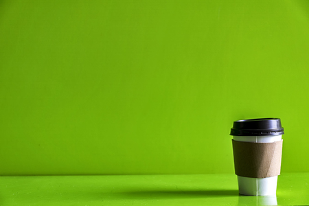Paper cup of coffee Isolated green background.There is a brown paper around the glass.To prevent heat.Space to enter text.The light to shine.