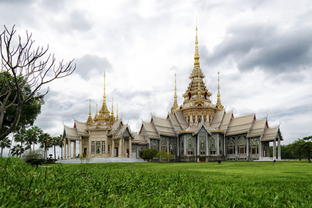 Main building of Non Kum Temple during daytime with a pool and background of cloudy blue sky,  Na-khon Rat-cha-si-ma, Thailand.