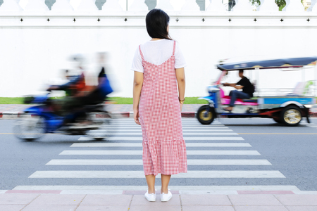 Women standing alone crossing the street crossing the crosswalk. Looking at the car on the road to safety. The car is driving through.