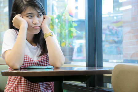 Sad girl, sit in a restaurant. Im thinking about the past. Now she needs morale. Waiting for a contact on a smartphone.