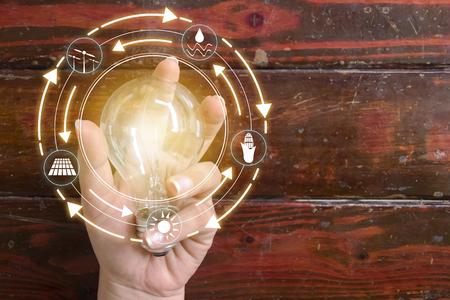 Hand, die Glühlampe vor globaler Show den Verbrauch der Welt mit Ikonenenergiequellen für erneuerbare, nachhaltige Entwicklung hält. Ökologiekonzept.