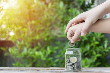 Kleines Mädchen und Stapelmünze zum Sparen. Geld sparendes Konzept. Mädchen und Mutter setzen Münzen in eine Glasflasche. Für eine gute Zukunft in Bildung und Finanzen. Dies ist der Beginn der Investition. Standard-Bild