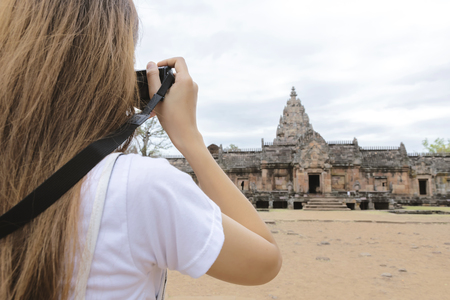 Travel concept. Women tourists are taking photos of tourist attractions White Castle Phanom Rung. Rock Castle in Thailand Beautiful Wild nature. Travel in Thailand