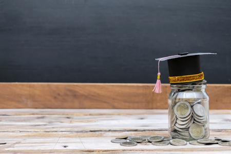 Bildungserfolgskonzept. Ein Glasgefäß mit vielen Münzen bis zum Überlaufen, Top mit einer Gradkappe. Der Hintergrund ist eine Tafel. Kostengünstige Investition mit guter Rendite. Standard-Bild