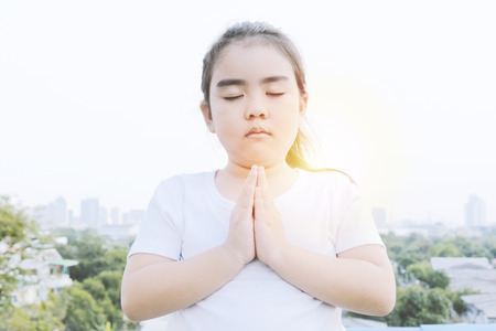 Praying to God with faith in that. Both exist and do not exist. It is a matter of faith and experience. Asian girl wearing a white shirt, High-angle house background. 写真素材
