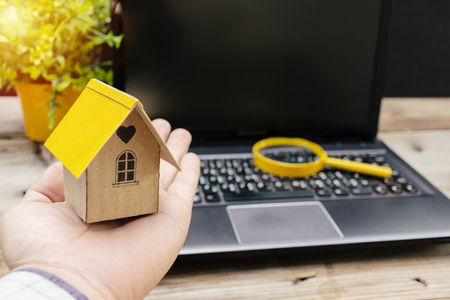 Searching for home concept. Model houses that are placed on hand and have glasses on notebooks. The background is a computer screen with free space to enter advertising messages.