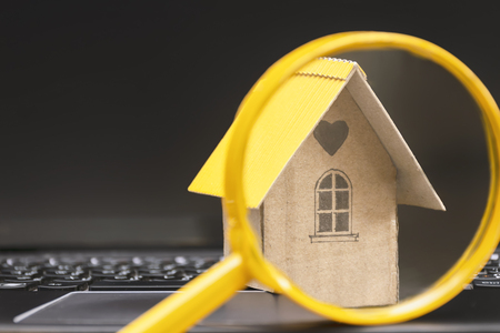 Searching for home concept. Model houses that are placed on notebooks and have glasses sold as front scenes. The background is a computer screen with free space to enter advertising messages. Imagens