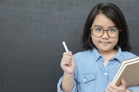 Education concept. A girl who plays a role as a teacher, Hand holding chalk and books. She wears glasses, The background is a blackboard. There is a blank space to put text into advertising media. Reklamní fotografie