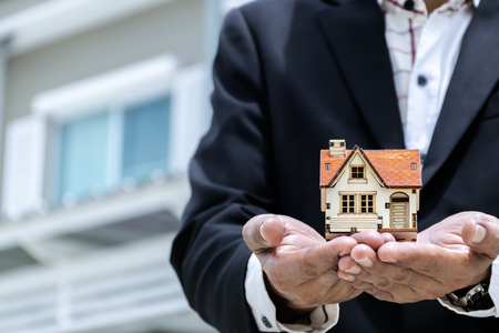 Home buying and selling agents. A businessman wearing a suit with a model house placed on his hand. Housing demand concept.
