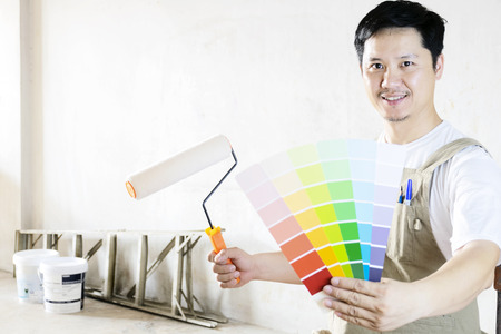 Painted home decoration concept. The painter is holding a paint roller, And color bars as examples in work. The background is an empty wall, With paint bucket and stairs.