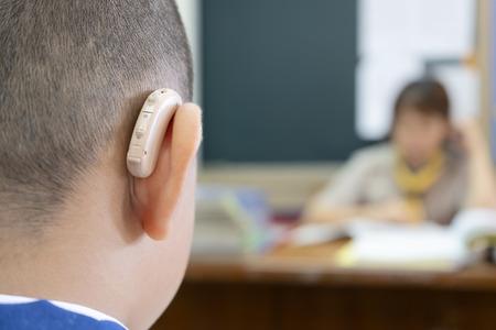 Studenti che indossano apparecchi acustici per aumentare l'efficienza uditiva. Aiuta essere in grado di imparare tanto quanto un amico. Lo sfondo è un insegnante che gli sta parlando.