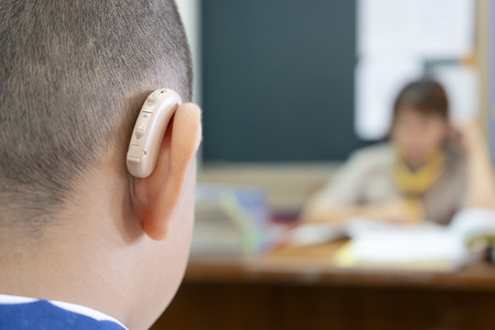 Students who wear hearing aids to increase hearing efficiency. Helps to be able to learn as much as a friend. The background is a teacher who is talking to him. 版權商用圖片 - 120477862