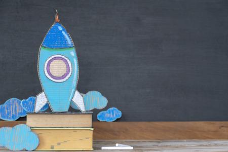 Retour au concept de l'école. Les fusées en papier sont situées sur des livres. Le fond est un tableau noir. Commencer à apprendre de nouvelles choses, à se développer pour réussir dans le futur. Banque d'images
