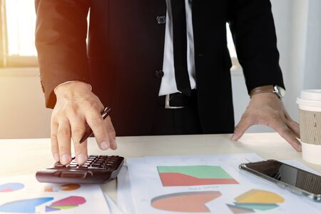 Businessmen are calculating with calculators to calculate costs and profits. Good marketing planning must be prudent. With analysis from graph statistics.