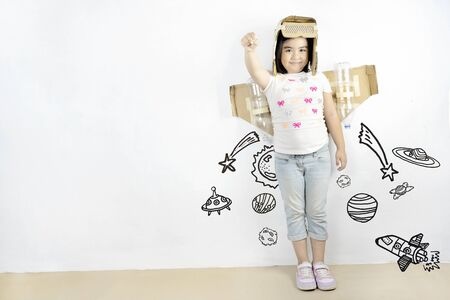 Cute Asian girls are enjoying playing as imagined, Is traveling to her dream. There is a helmet and jets wings made of crate paper. Isolated white background. Graphic images were created.