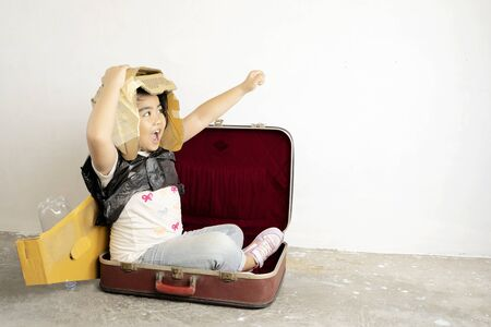 Cute Asian girls are enjoying playing as imagined, Is traveling to her dream by sitting in a suitcase. There is a helmet and jets wings made of crate paper. white background. Imagens